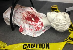 Mannequin lying on the floor, wearing a white t-shirt covered in fake blood & surrounded by yellow