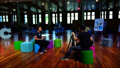 Holly from fizzics being interviewed by man with camera and woman on colourful stools in a hall