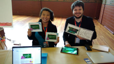 Aurora Reality man and woman holding books behind a desk with laptop and tablet