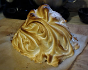 Brown and white mountain of meringue on a pieces of white baking paper on a wooden board