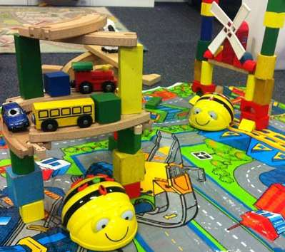 Beebots moving along a road map with wooden blocks