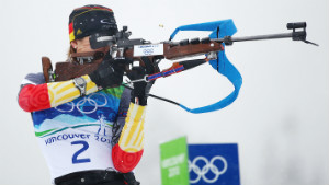 biathlon athlete holding a rifle ready to shoot Olympics logo and white snow background