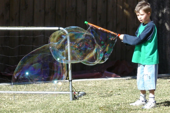 Boy making big bubble larger than himself in a backyard