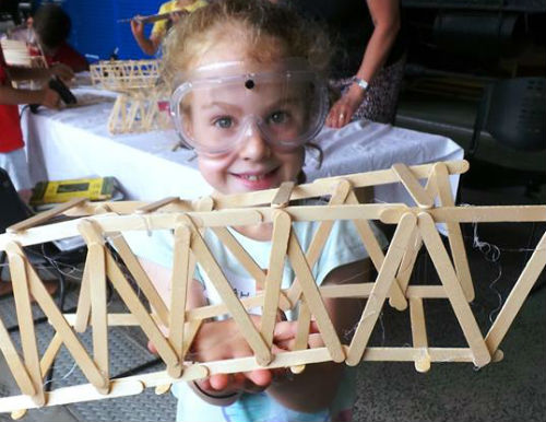 Building bridges using paddle pop wooden sticks. A girl in this photo is wearing safety glasses and smiling whilst holding up her bridge design