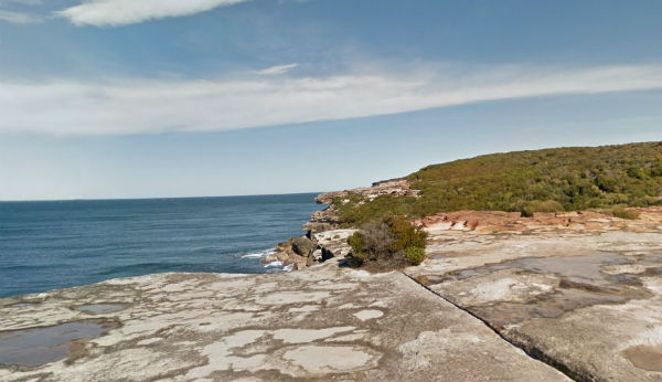 Coast walk in the Royal National Park., showing the sea, a cliff and heath shrubs