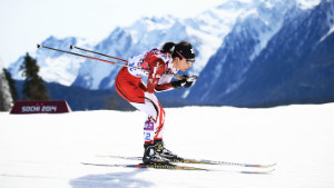 Cross country skiing athlete going down hill crouched mountains and snow in background