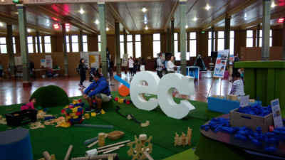 Indoor playground with green mat and kids playing with toys and parents looking on, big white letters ec people walking around