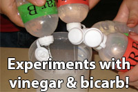 Title - Experiments with vinegar and bicarb soda (showing three bottles of liquid being squirted into a beaker)