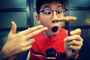 Boy with black rimmed glasses looks in awe , one hand pointing at other hand holding a pencil with a fidget spinner balanced on top
