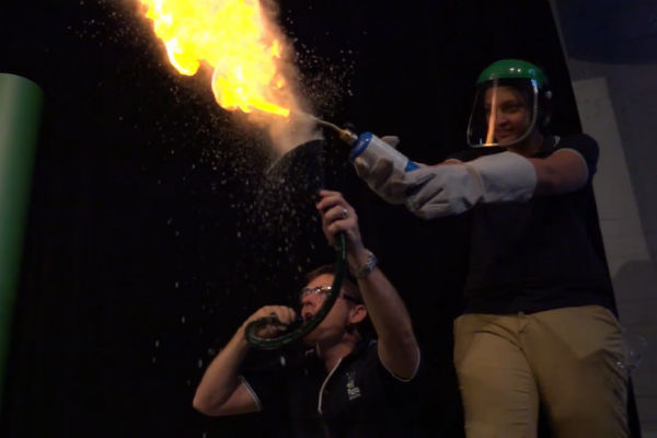 Holly from Fizzics wearing face shield and gloves while holding blow torch with Ben crouched next to her blowing flour through a hose and funnel making a large yellow fireball