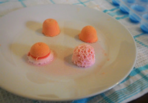 orange bicarb blobs and vinegar on a white plate, some covered in white foam