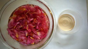 pink petals steeping in water inside clear pyrex bowl, next to it a small plastic container with a little bit of clear yellow liquid