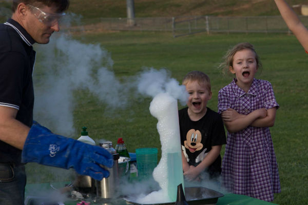Ben from Fizzics wearing safety glasses and blue gloves demonstrating liquid nitrogen experiment large measuring cylinder fog children watching