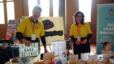 little bang science children's discovering museum Man and woman in yellow shirts standing behind table full of toys