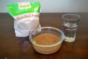 A bag of psyllium husk powder, a glass of water and a small glass bowl filled with brown goop