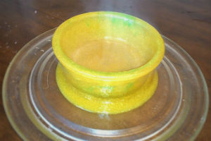 yellow slime in a bowl overflowing onto a glass microwave plate on a brown table
