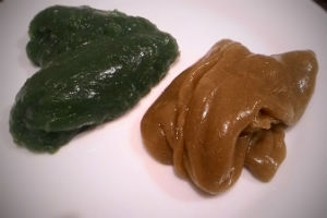 Dark green flubber and brown flubber on a white plate
