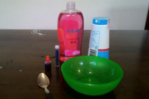 A bottle of pink hand soap, a green bowl, red food colouring, bottle of blue glitter, a spoon and a shaker of salt on a brown table