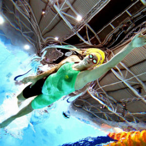 Commonwealth games swimmer in green and black mid stroke in the water looking up from bottom of pool