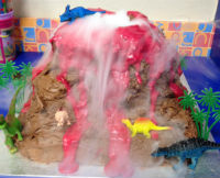 Volcano cake with dry ice fog pouring down the side. Plastic dinosaurs & trees surround the chocolate cake