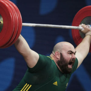 Australian weightlifter in green shirt lifts red weights at commonwealth games