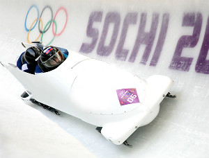 Two people wearing black helmets in a white bobsleigh on a track with Olympic games logo and sochi