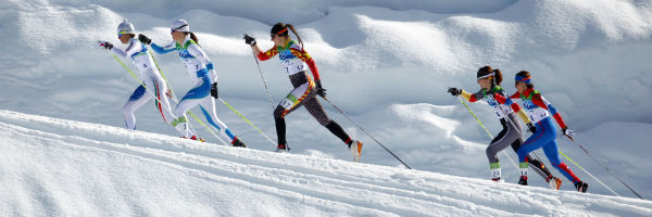5 female olympic cross country skiers skiing uphill in white snow white clouds in the background