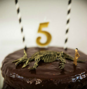 Chocolate dinosaur party cake, with a palaeontoligst figurine looking over a dinosaur replica lying on it's side