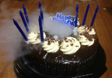 Dry ice fog coming out of a chocolate cake with blue candles