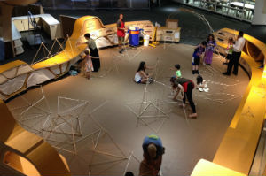 nySci Maker space, view from above with kids building structures out of lengths of wood