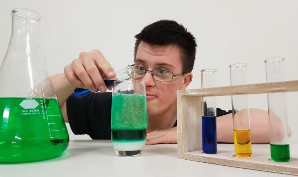 scienceability - student pouring blue liquid into a fizzing green test tube