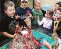 Kids excited around a smoking volcano cake made out of chocolate
